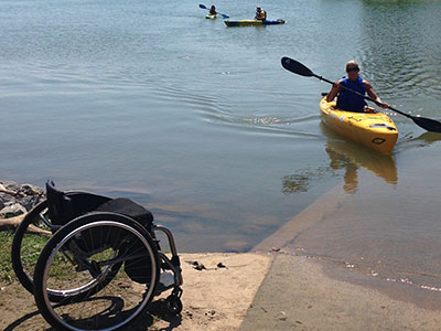 Kayaker on the water; wheelchair on the beach