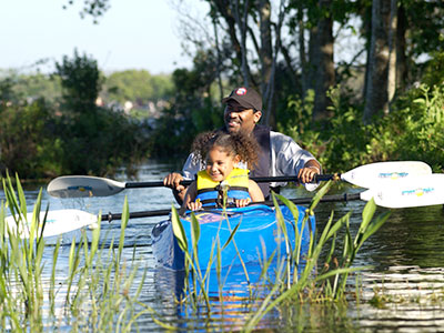 Smiling family kayaking in marsh