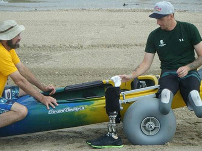 Getting into adaptive kayak on the beach