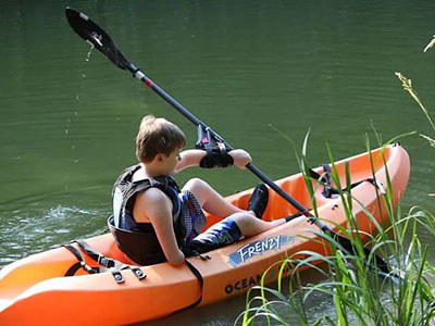 One-armed paddler in kayak on the water, adaptive paddling