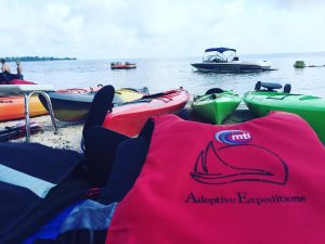 Image of kayaks on a beach with Adaptive Expeditions' logo.